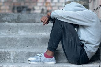Lonely male teen sitting building stairs, misunderstanding depression, problem